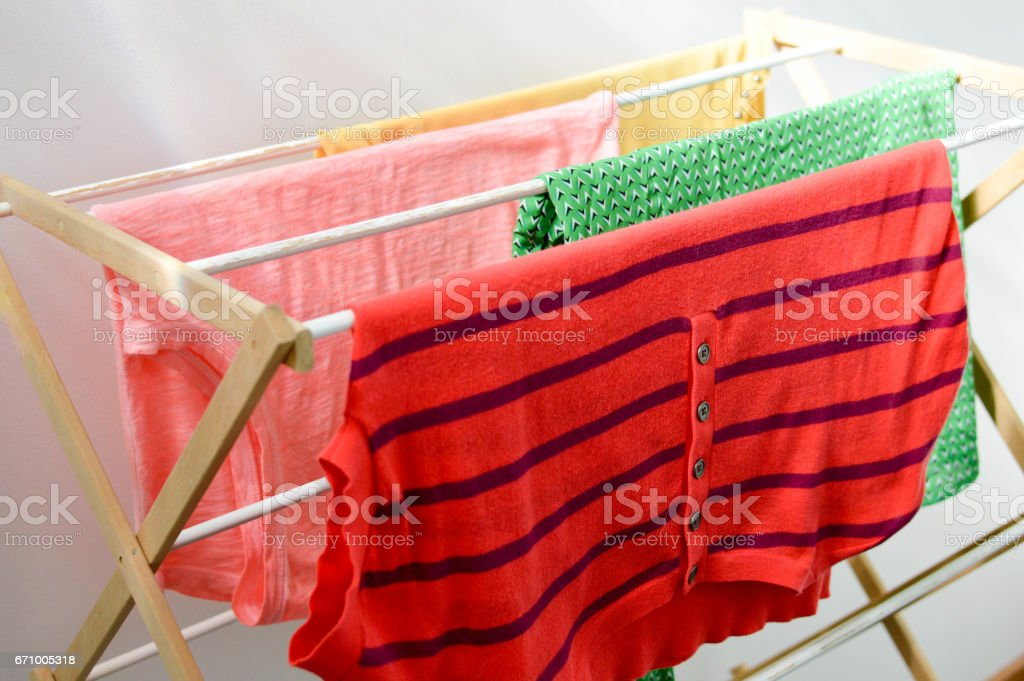 Laundry Drying on a Clothes Rack Indoors stock photo