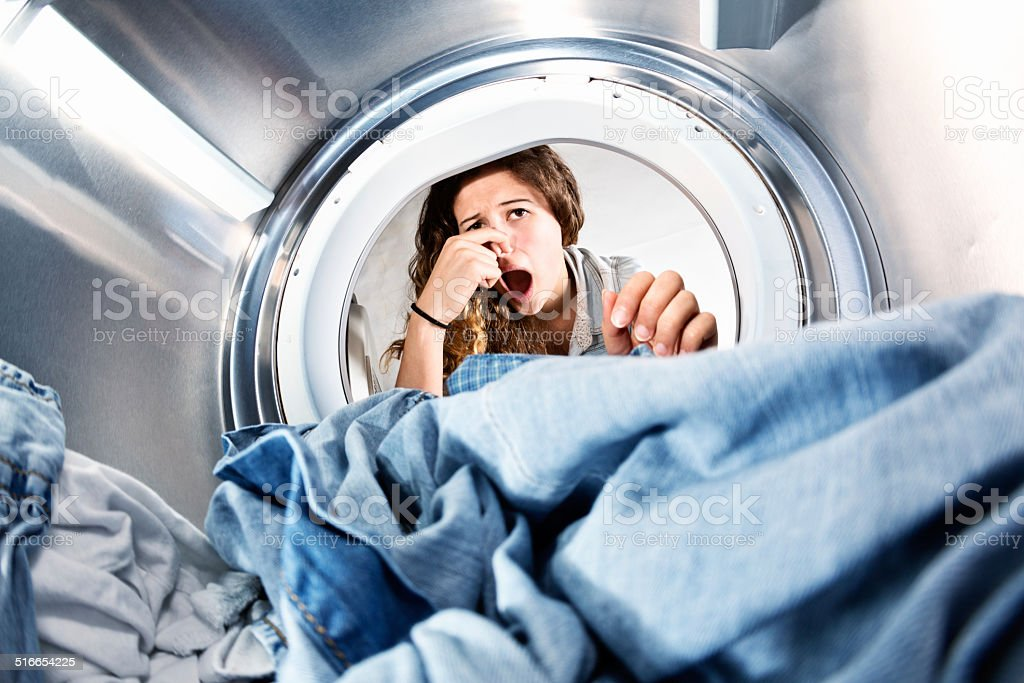 Laundry left in clothes dryer stinks! Unhappy woman holds nose. stock photo