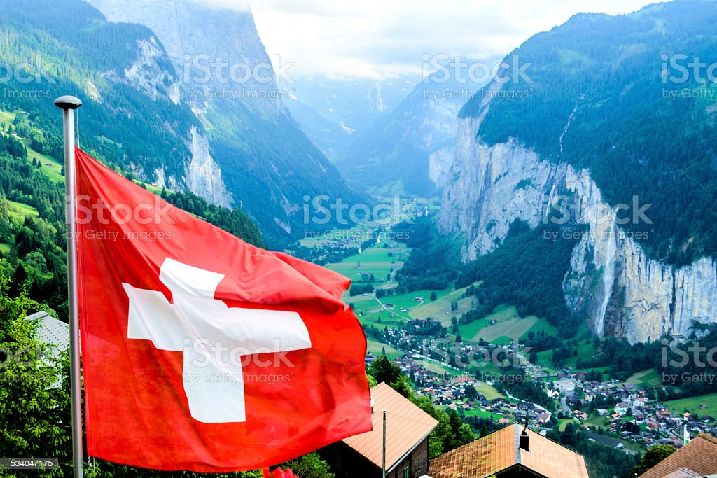 Lauterbrunnen Valley in the Bernese Oberland, Switzerland with Swiss Flag stock photo