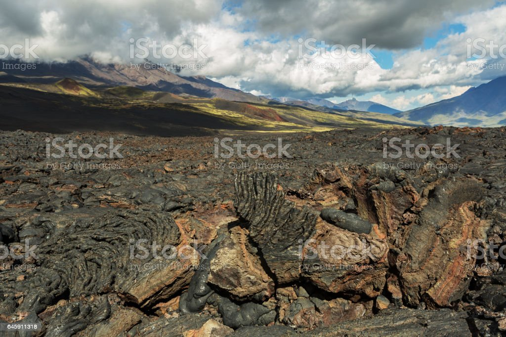 Lava field at Tolbachik volcano, after eruption in 2012 on background Big Udina volcano and Plosky Tolbachik volcano, Klyuchevskaya Group of Volcanoes stock photo