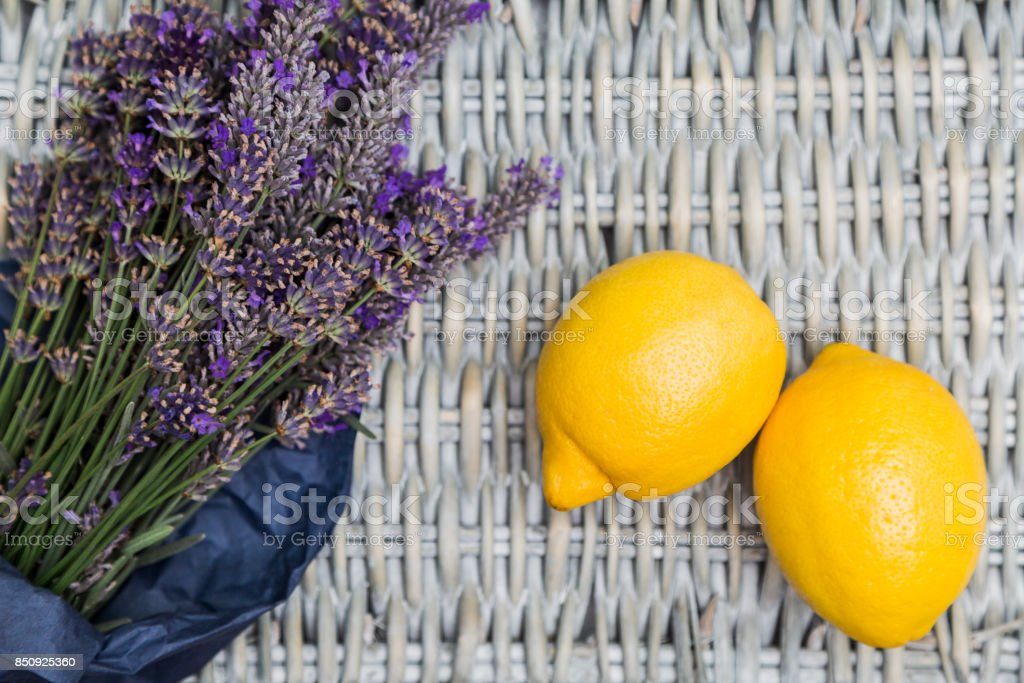 Lavender bouquet with lemons on wicker background stock photo