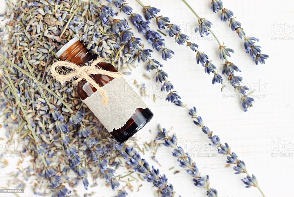 Lavender essential oil bottle on dried flowers stock photo