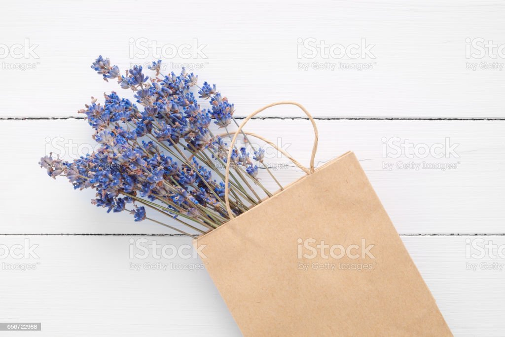 Lavender in shopping paper bag on white table. stock photo