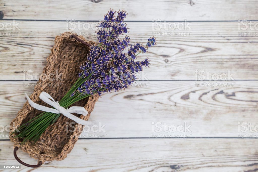 Lavender in wicker basket on wooden background stock photo