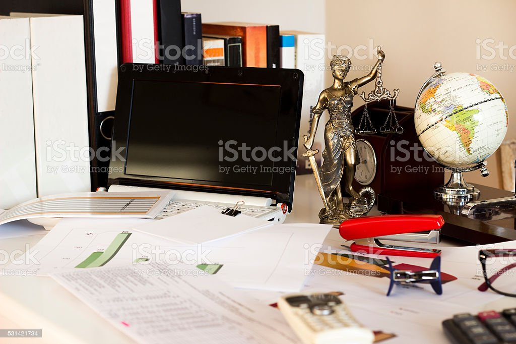 Law and business concept, statue, world map and laptop stock photo