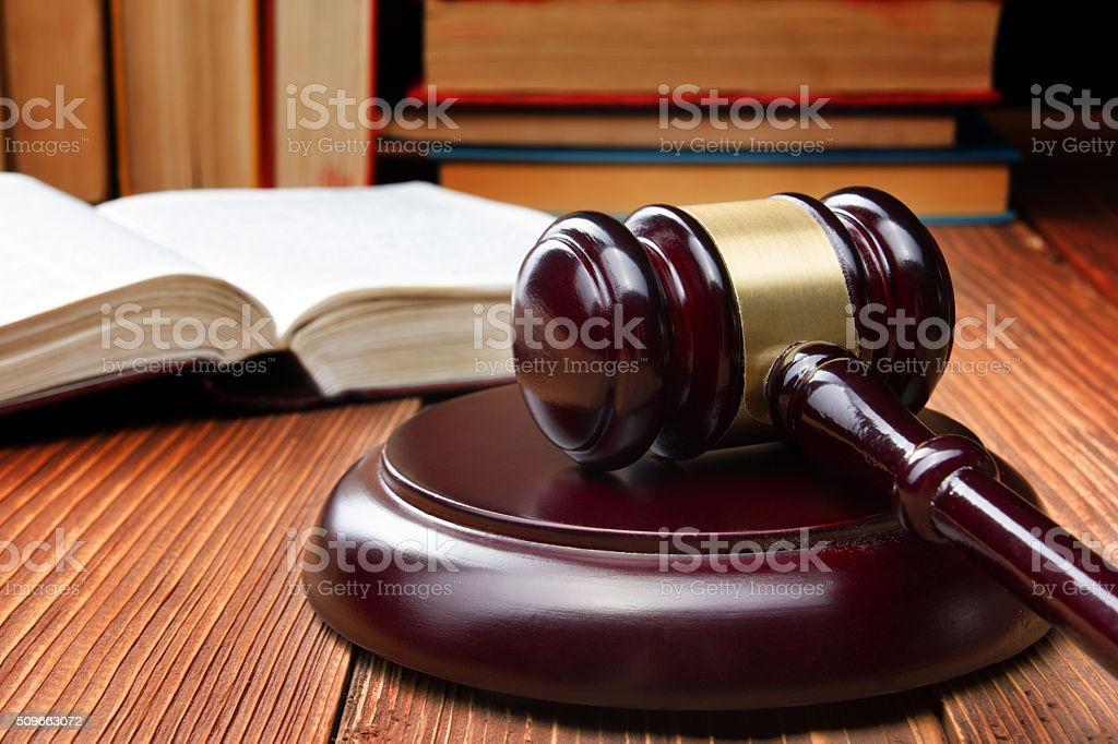 Law book with wooden judges gavel on table in a stock photo