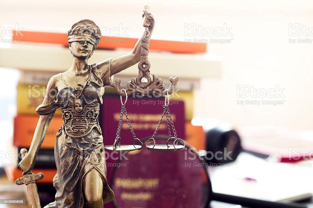 Law concept, statue, magnifying glass, passport and book stock photo