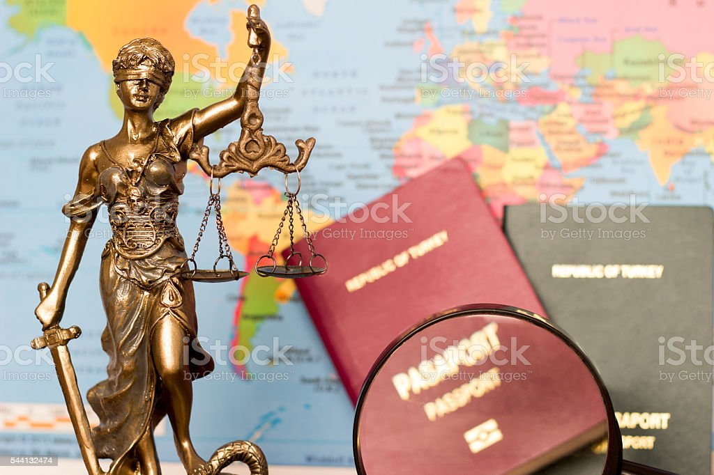 Law concept, statue, magnifying glass, passport and world map. Travel stock photo