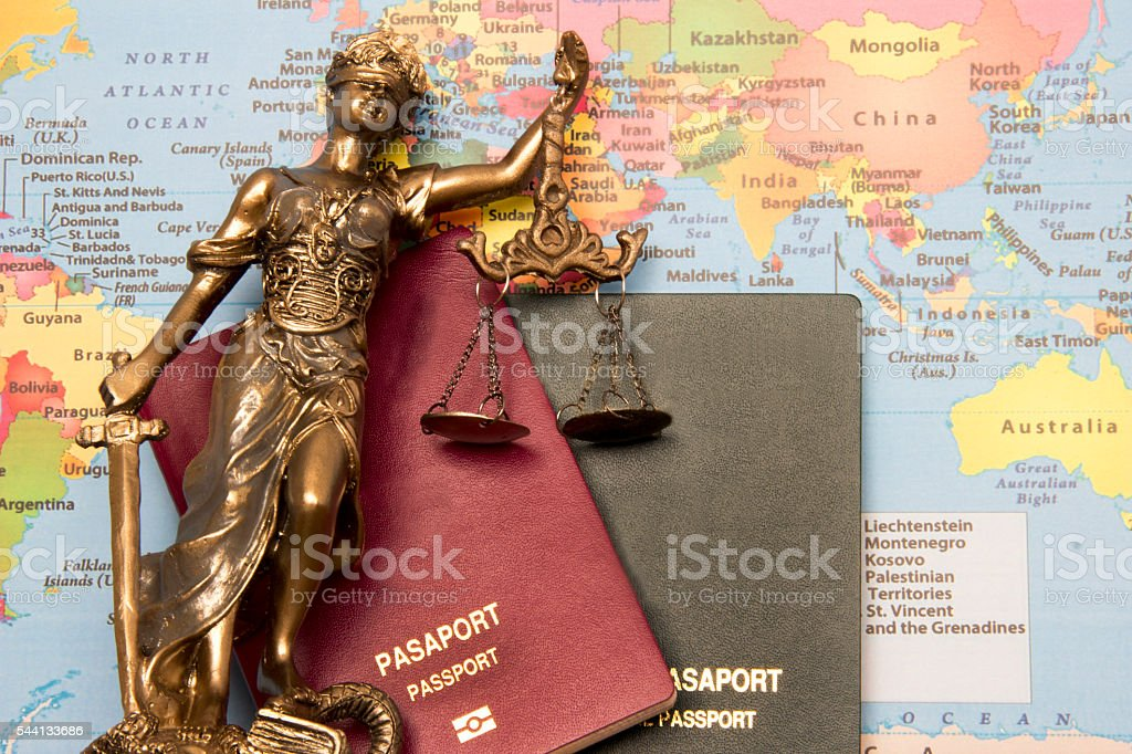Law concept, statue, passport and world map. Travel stock photo