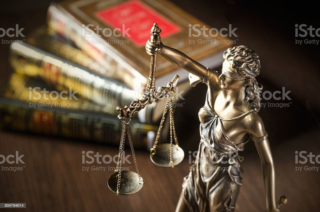 Law concept with Themis and books in background stock photo
