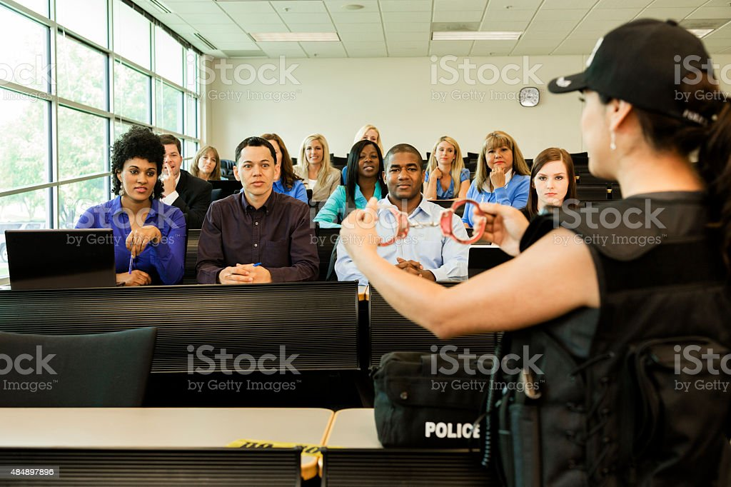 Law:  Policewoman speaks to police cadets in classroom. Handcuffs stock photo