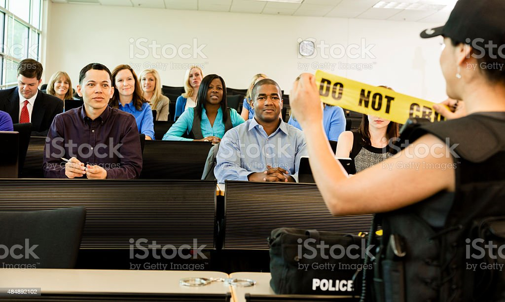 Law:  Policewoman speaks to police cadets in classroom. stock photo