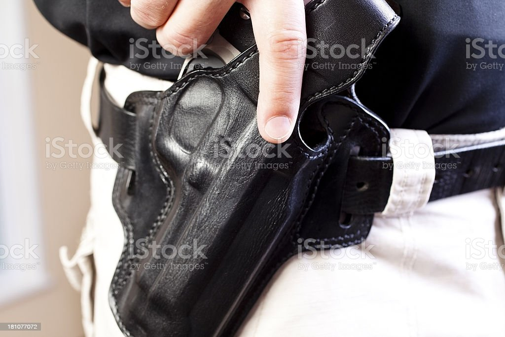Law: Undercover detective ready to draw gun weapon from holster stock photo