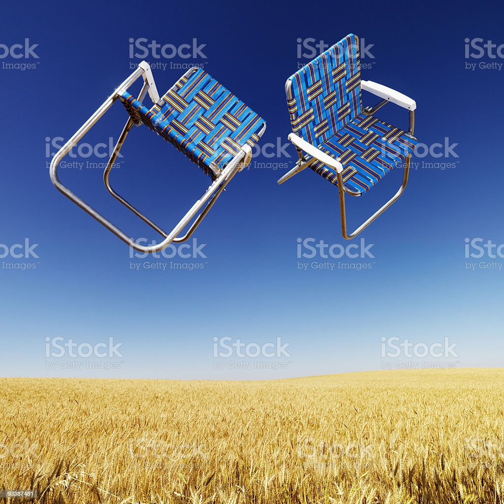 Lawn chairs over wheat field. royalty-free stock photo