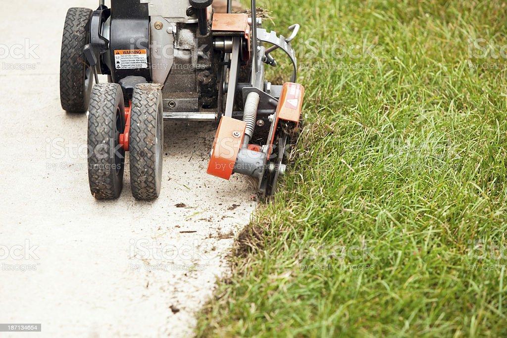 Lawn Edger Machine Edging Grass next to Sidewalk royalty-free stock photo