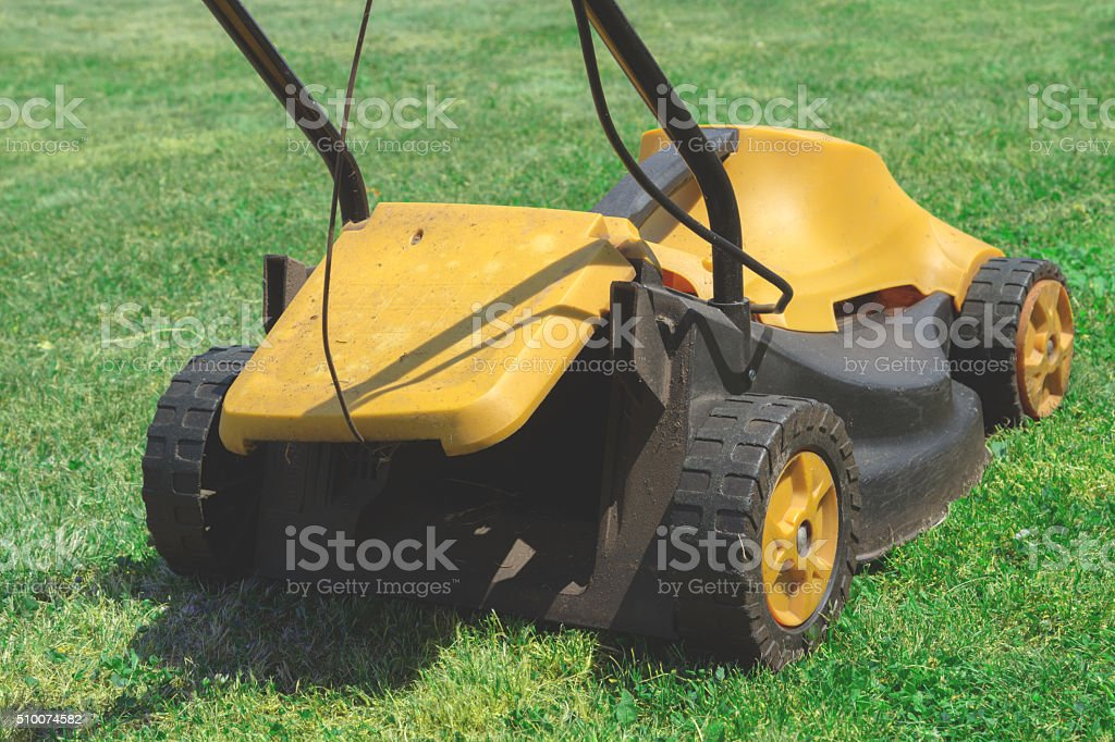 Lawn mover on a green grass field. stock photo