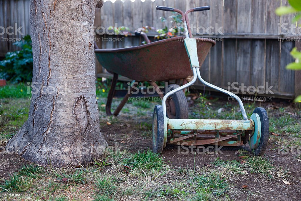 lawn mower leaning against wheel barrow stock photo