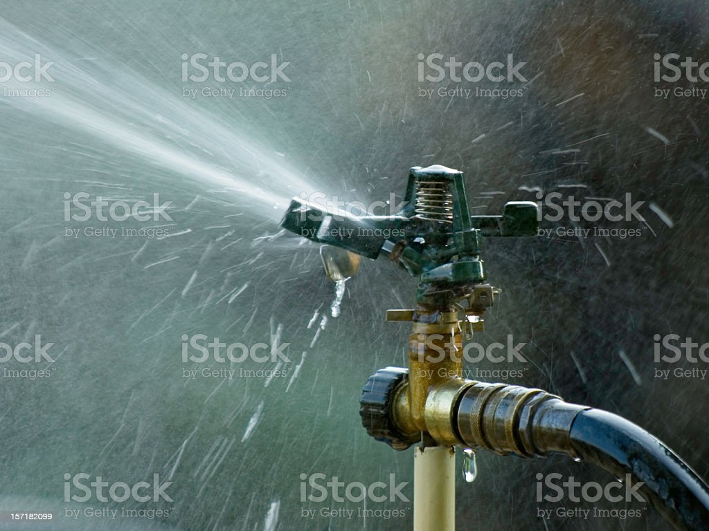Lawn sprinkler with water coming out of it stock photo