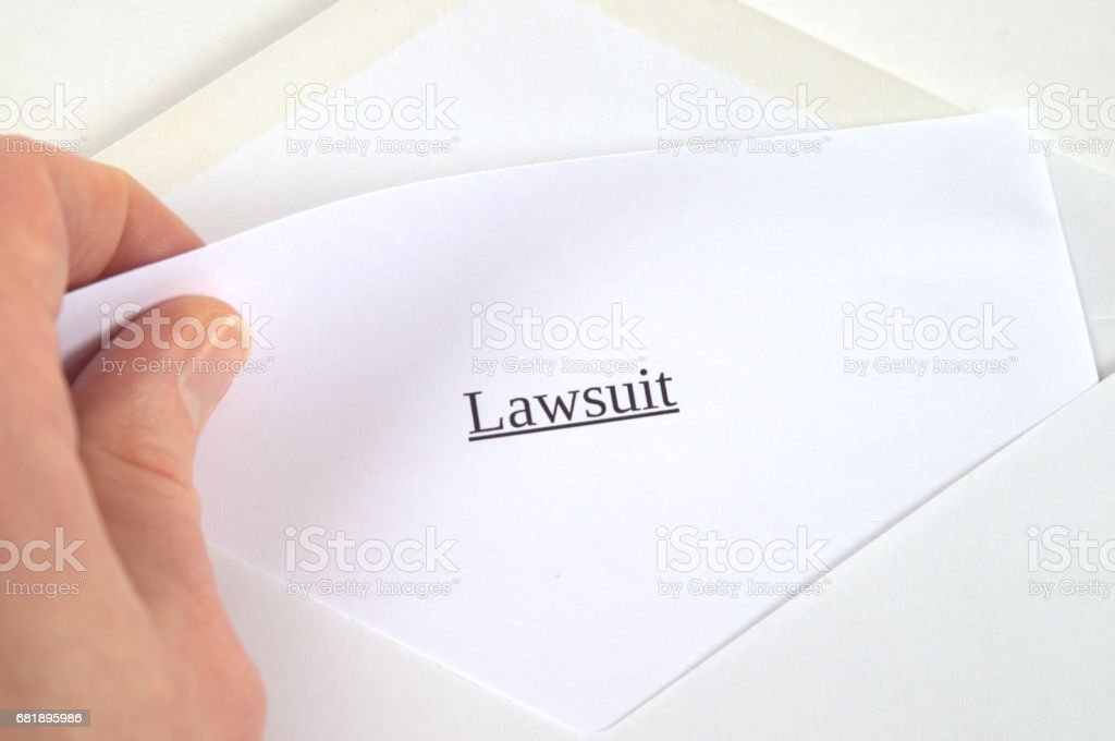 Lawsuit printed on white paper and envelope, hand holding it, white background stock photo