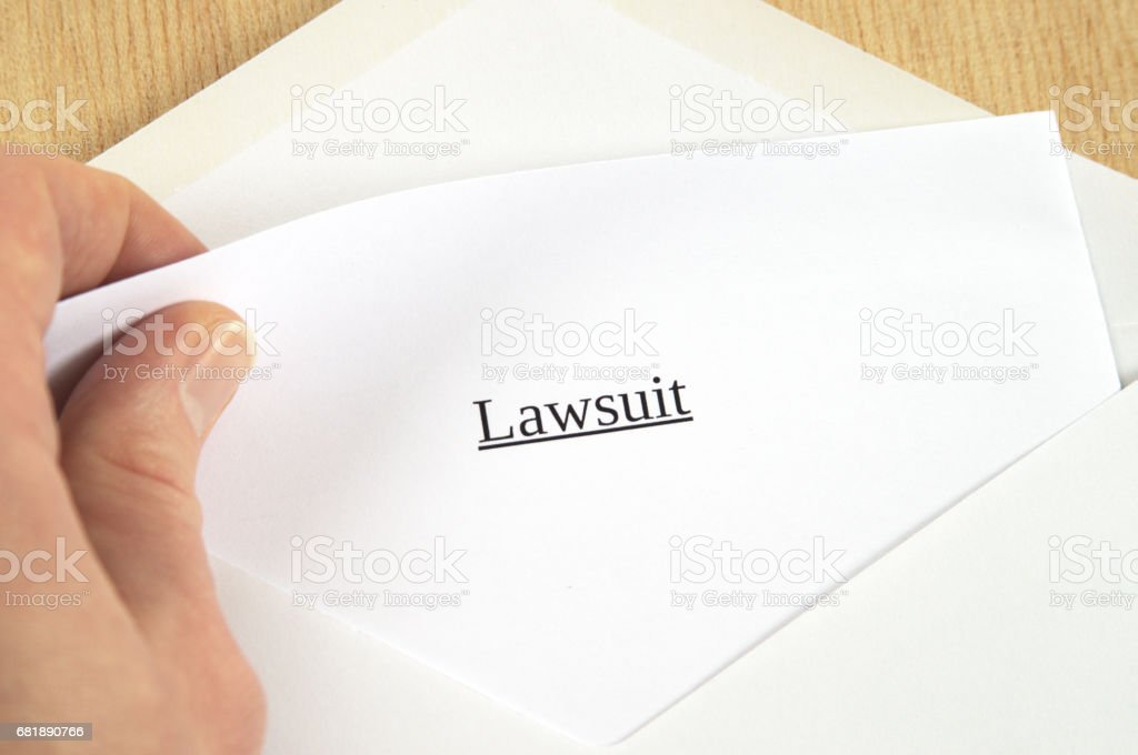 Lawsuit printed on white paper and envelope, hand holding it, wooden background stock photo