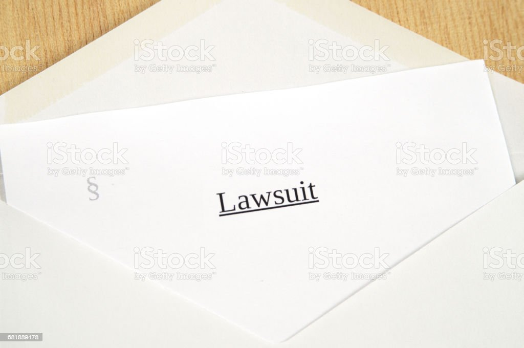Lawsuit printed on white paper and envelope, wooden background stock photo