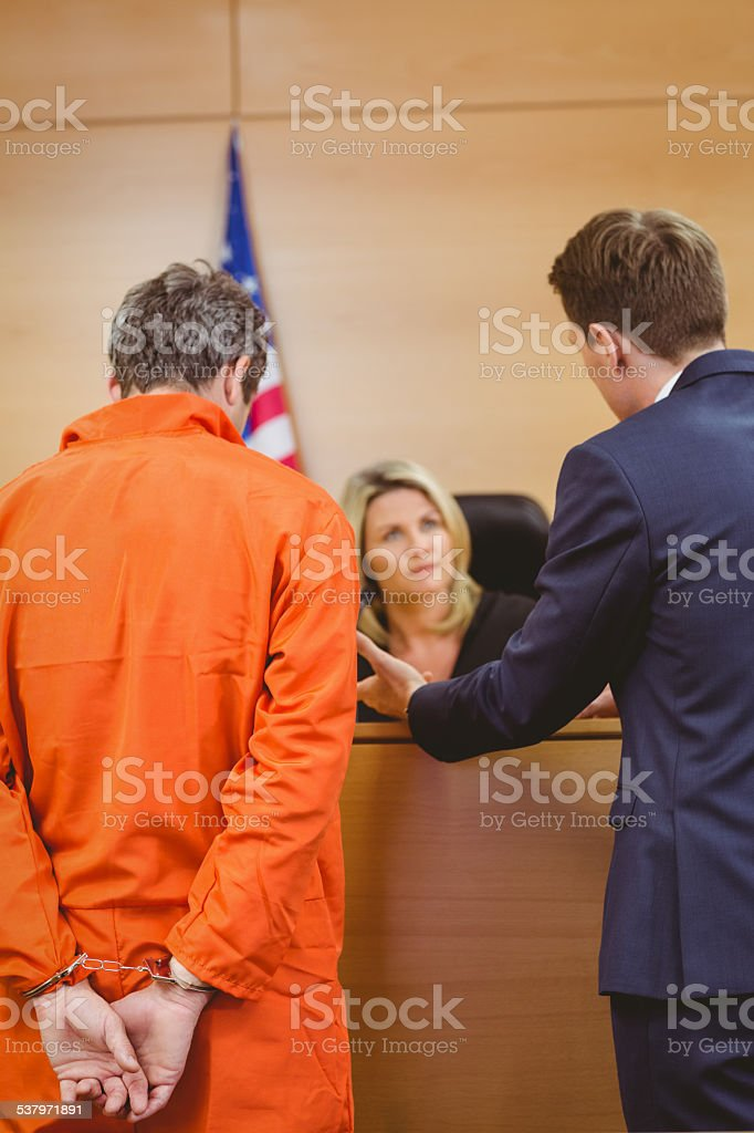 Lawyer and judge speaking next to the criminal in handcuffs stock photo