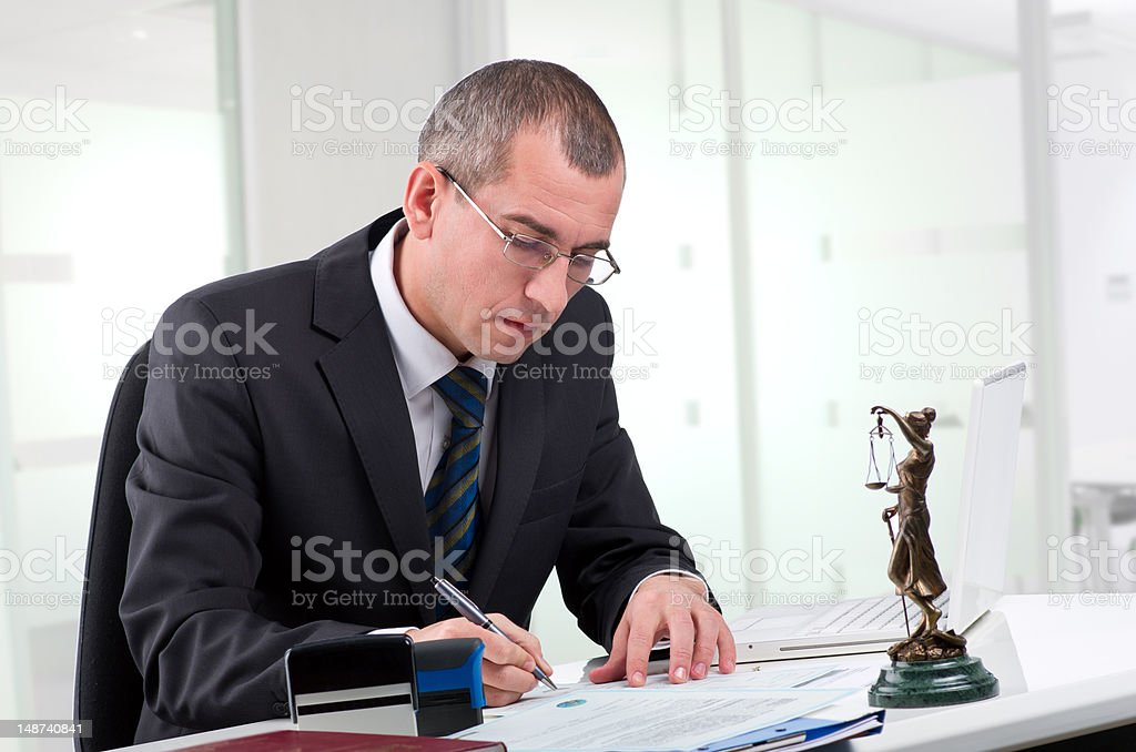 A lawyer at a desk with a statue of lady justice nearby royalty-free stock photo