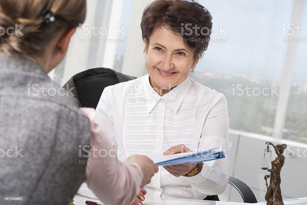 Lawyer giving documents to client at her office stock photo