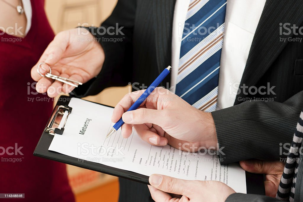 A lawyer handing the keys to his client as they sign papers stock photo