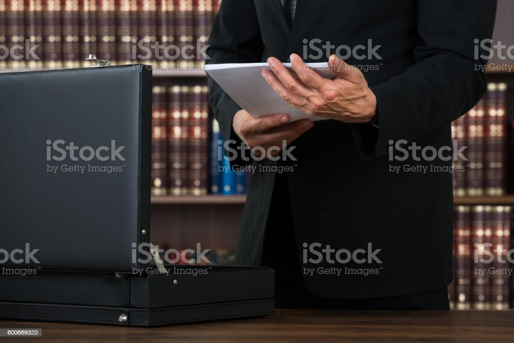 Lawyer Keeping Documents In Briefcase In Office stock photo