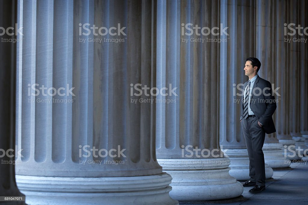 Lawyer Or Banker Standing Next To Large Columns stock photo