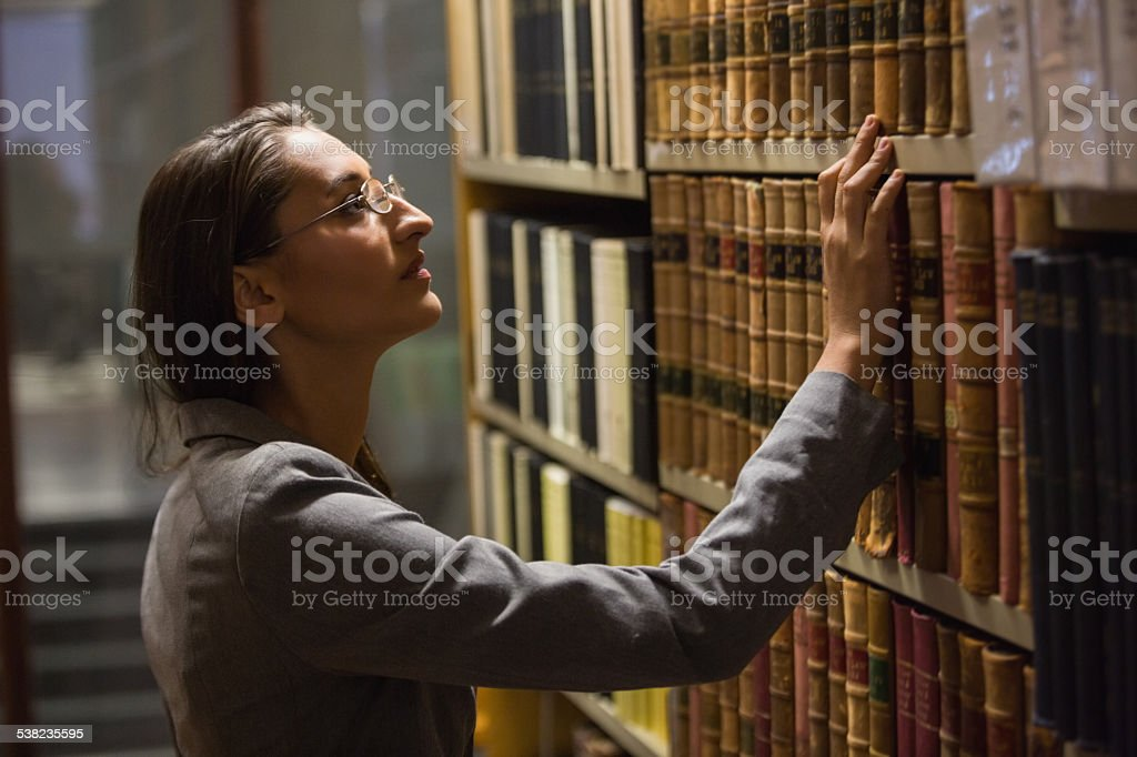 Lawyer picking book in the law library stock photo