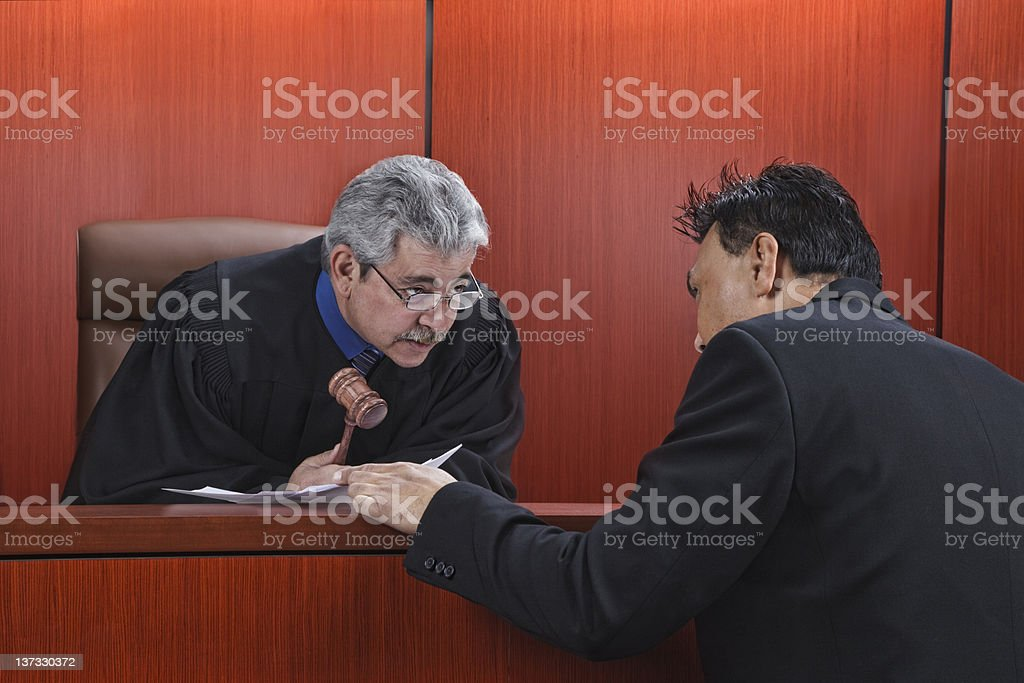 Lawyer Speaking With Judge in Courtroom stock photo