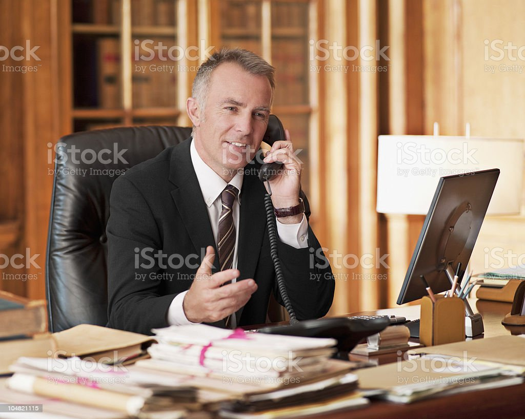 Lawyer talking on telephone and gesturing in office stock photo