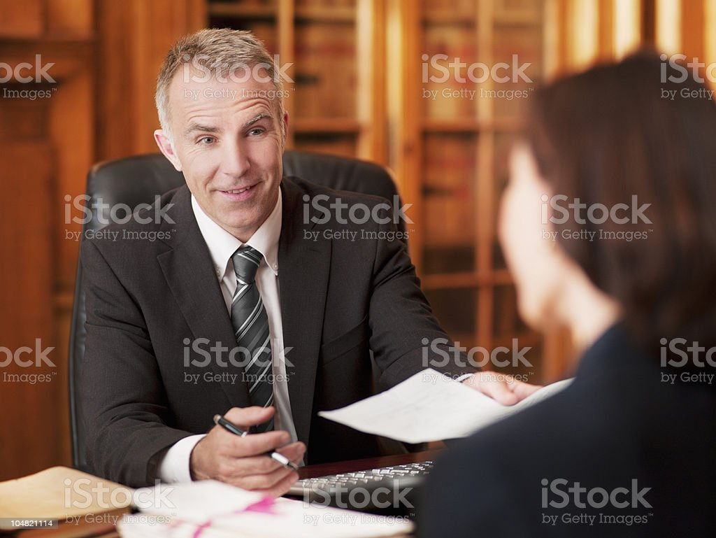 Lawyers exchanging paperwork in office stock photo