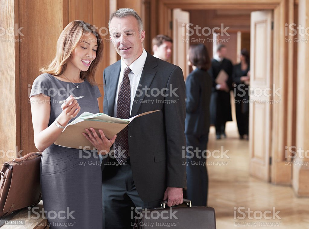 Lawyers reviewing case file in corridor stock photo