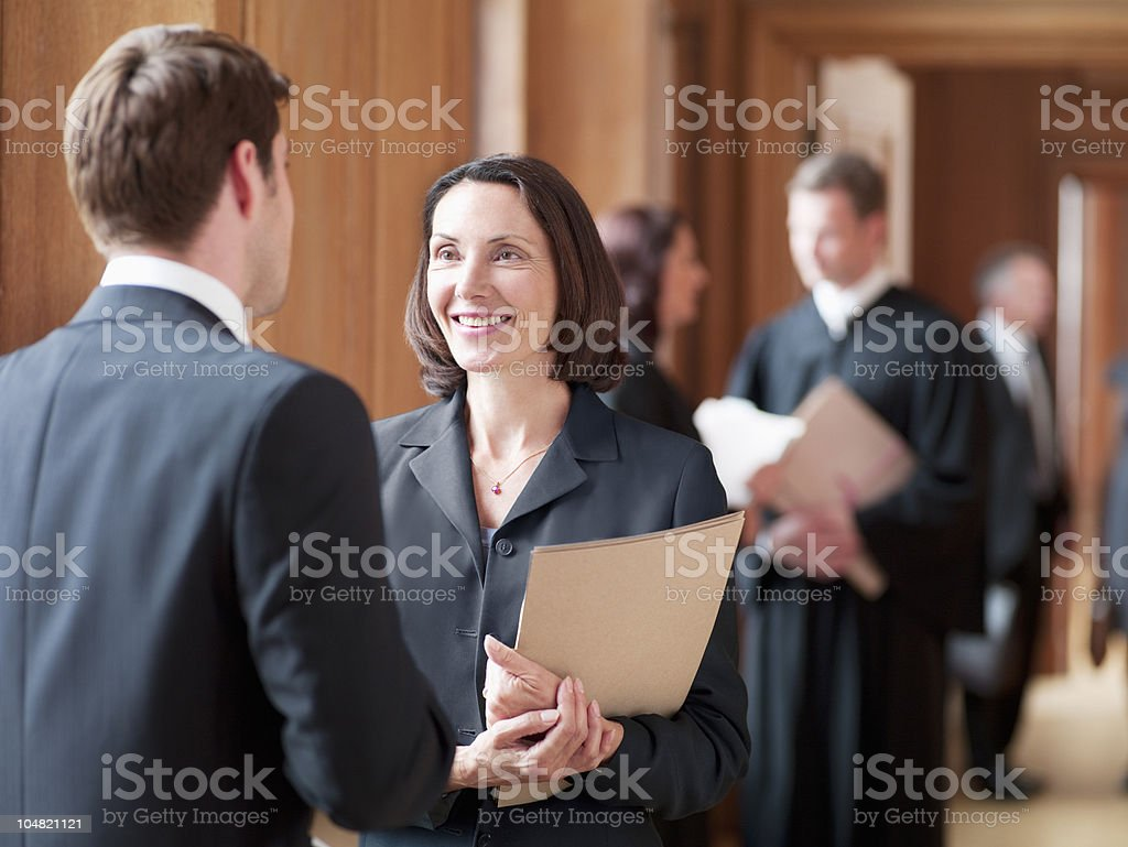Lawyers talking in corridor stock photo