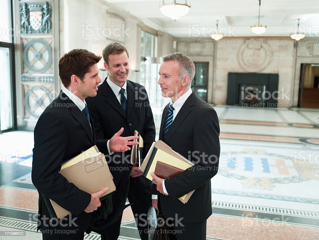 Lawyers with files talking in lobby stock photo