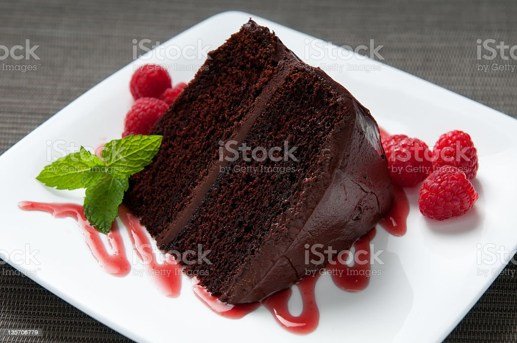 Layered Chocolate Cake with Frosting, Raspberries, Sauce and Mint royalty-free stock photo