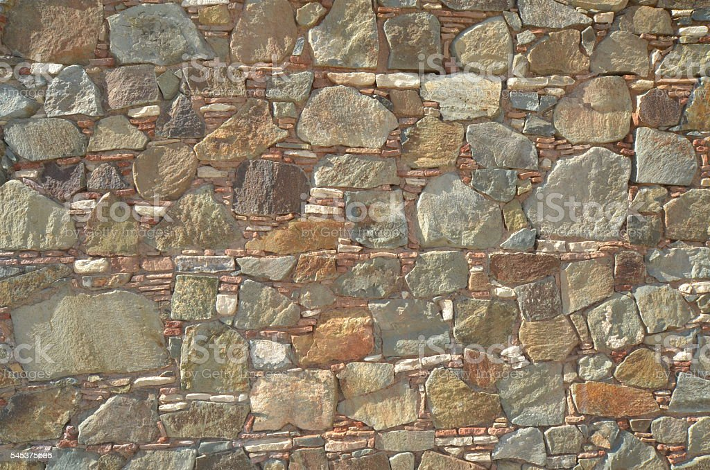 Layered construction on rock wall with vairous natural stone types stock photo