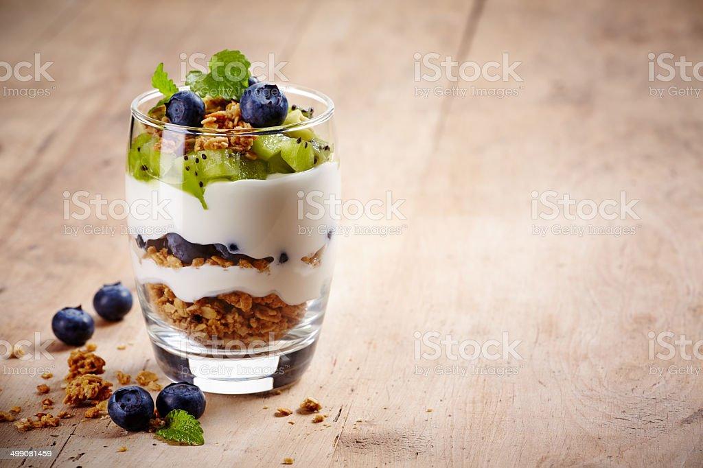 Healthy layered dessert with cream, muesli, kiwi and blueberries on...