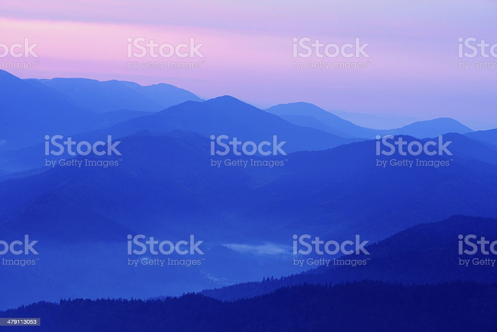 Layered mountain landscape in blue twilight stock photo