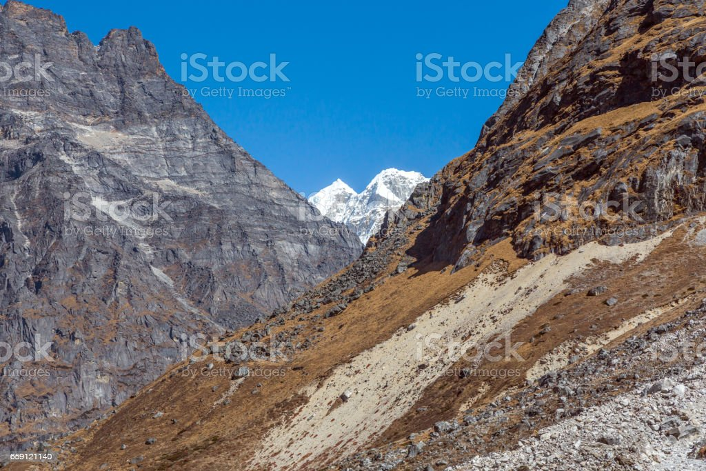 Layered Mountain Terrain with Rocks Grass and Snow stock photo