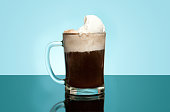 Layered Root beer float in a glass mug with dim blue back