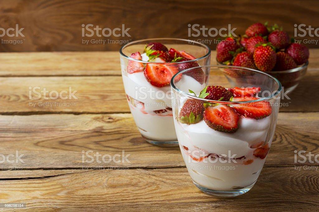 Layered strawberry dessert on wooden background stock photo