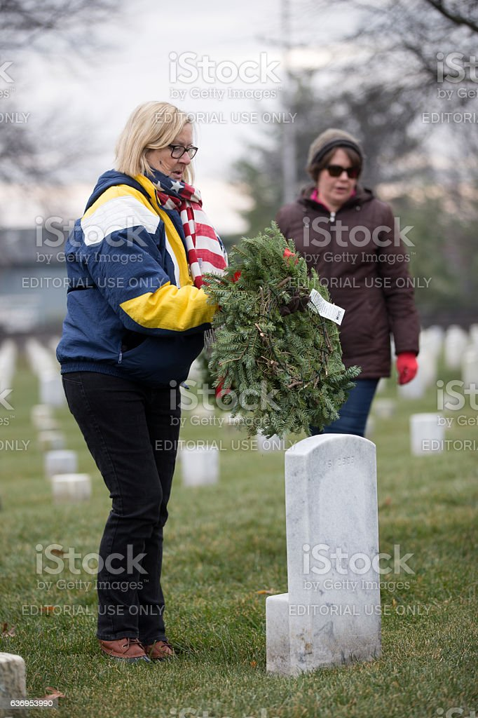 laying a wreath on a veteran's grave stock photo