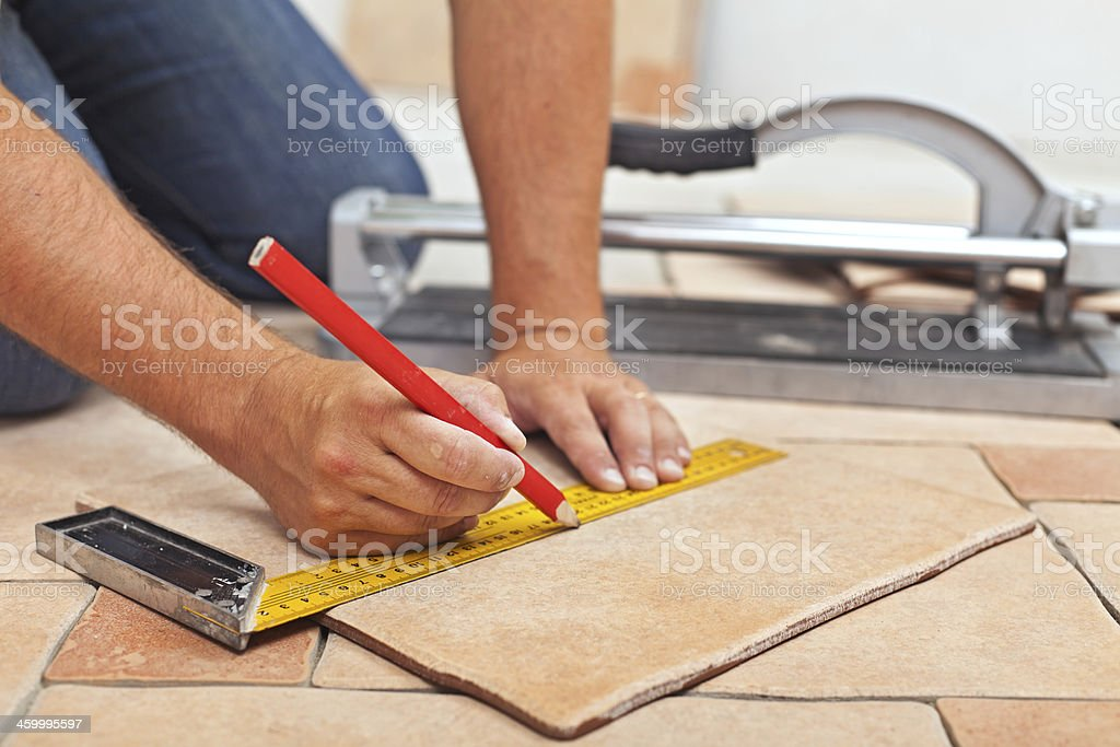 Laying ceramic floor tiles - man hands closeup stock photo