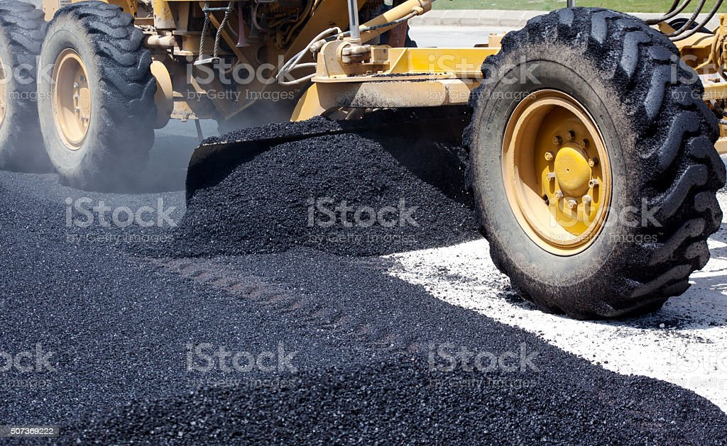 Laying fresh asphalt on construction site stock photo
