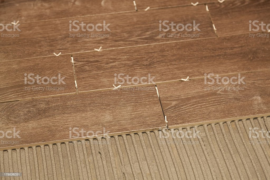 Laying wood effect ceramic floor tiles. stock photo