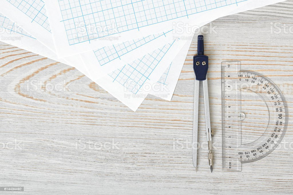 Layout with compass, protractor and graph paper on wooden surface stock photo
